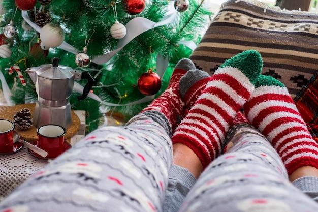 自宅のリビングルームのクリスマスツリーの横にあるソファでリラックスしたロマンチックなカップルの足カップルソックス