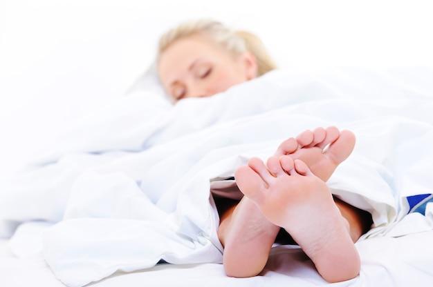 ベッドカバーの下から突き出ている寝ている女性のクローズアップの足