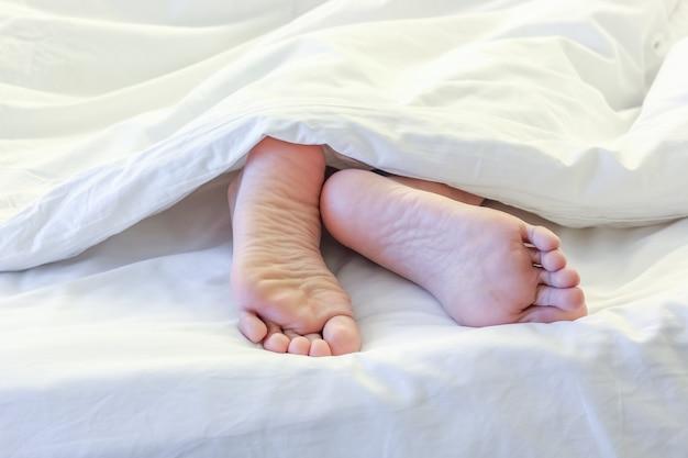 하얀 침대 방에서 잠자는 여자의 발