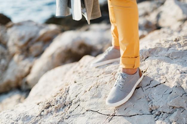 海の上の石の崖のシーンにひもで締められたスニーカーの新郎の足