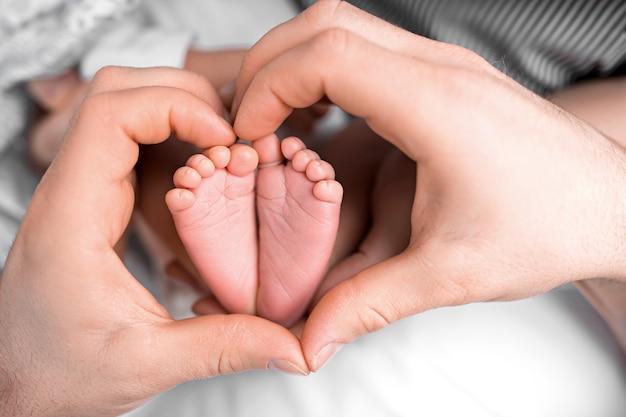 엄마의 손에 있는 신생아의 발을 닫습니다. 마음. 엄마와 그녀의 아이. 모성의 아름다운 개념적 이미지입니다. 고품질 사진