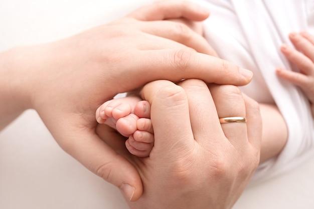 母親の手に生まれた新生児の足。母親は赤ちゃんの足を手に持っています。幸せな家族の概念。高品質の写真