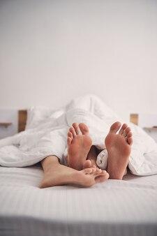 Ноги двух человек расслабляются в постели, накрытой белым одеялом