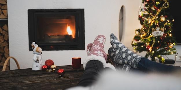 暖炉とクリスマスツリーの横に休日の装飾が施された素朴な木製の机の上に暖かい靴下を履いた2人の女性の足。
