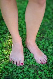 Ноги молодой женщины босиком ходить по свежей зеленой траве в солнечное лето утром