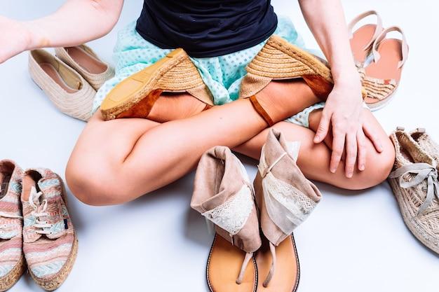 靴に囲まれて他の人を保持している夏のサンダルの若い女性の足。靴屋のコンセプト。靴の選択。靴の買い物