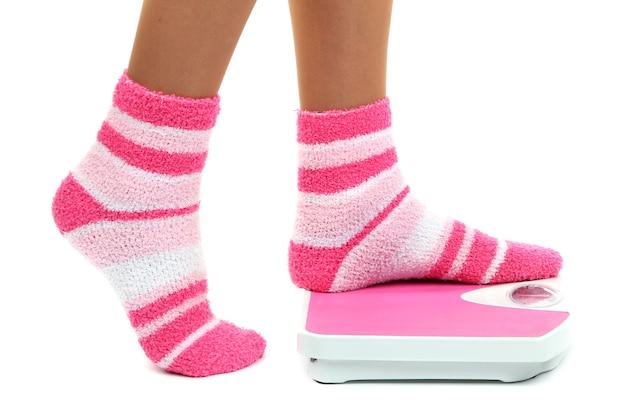 Ноги на весах, изолированные на белом фоне