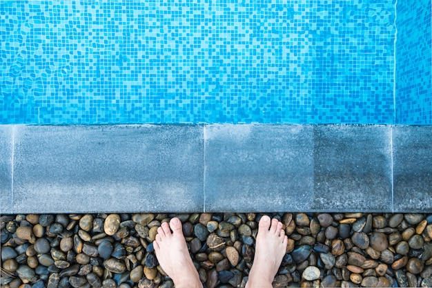 Feet at the pool side with blue mosaic tiles of swimming pool.