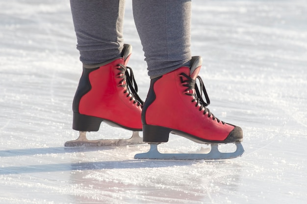 Feet in red skates on an ice rink. hobbies and leisure. winter sports