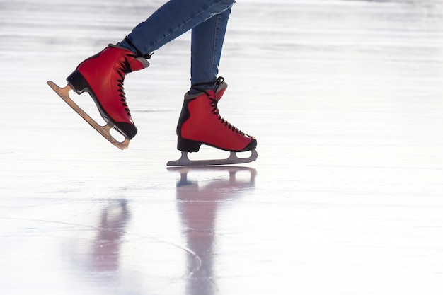 Feet in red skates on an ice rink. hobbies and sports. vacations and winter activities.