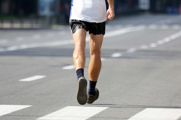 Feet running athlete at the distance of a marathon. sport and victory