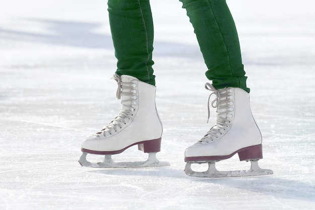 스케이트장에서 스케이트를 타는 발 스케이팅 소녀. 스포츠 및 엔터테인먼트. 휴식과 겨울 방학.