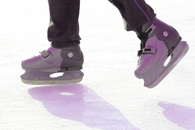 아이스링크에서 스케이트를 타는 발. 스포츠 및 엔터테인먼트. 휴식과 겨울 방학.