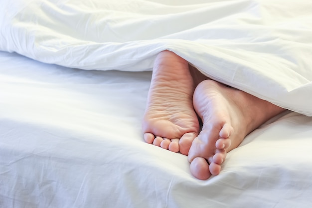 Feet of sleeping woman in the bed