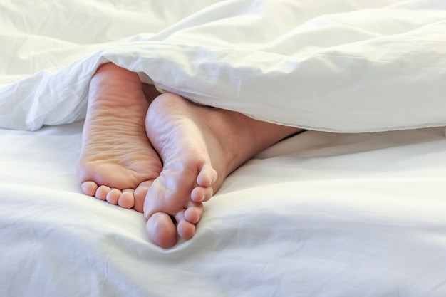 Feet of sleeping woman in white bedroom