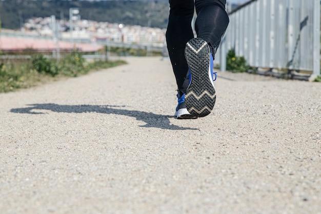 Feet of sporty man on park lane outdoors