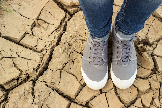 Feet standing on the chapped soil with crack