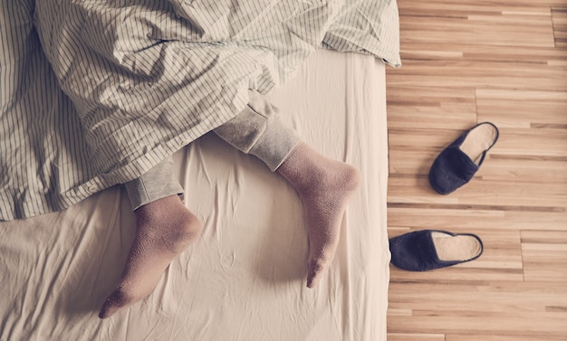 Feet sticking out of the duvet while a person sleeps on the bed, wooden floor, and slippers