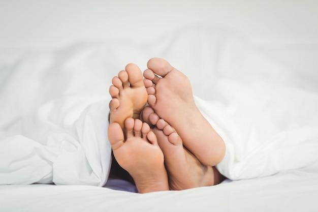 Ноги торчат из одеяла в спальне