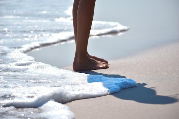 Feet walk on the beach sand. walking people on the seashore.