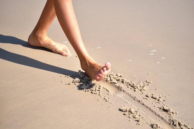 Feet walking on the beach sand. walking people on the seashore.