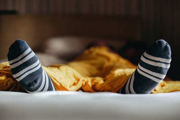 Feet in warm socks under the cover on the bed