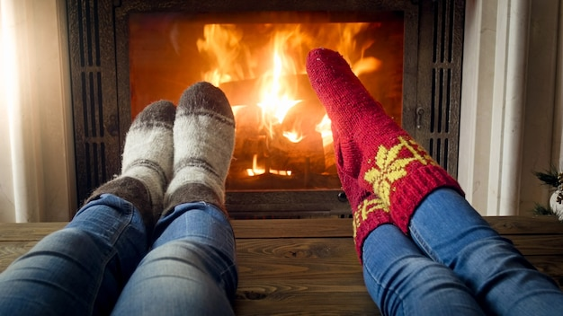 Feet wearing knitted wool socks warming by glowing fire at fireplace