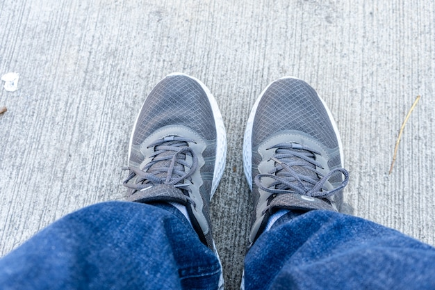 위에서 본 콘크리트 바닥에 흰색 땅딸막한 밑창 운동화와 청바지를 입은 발. 활동적인 라이프스타일, 피트니스 및 스포츠를 위한 새로운 편안한 신발. 공간을 복사합니다. 평면도.