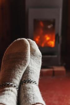 Feet in winter wool socks at fireplace