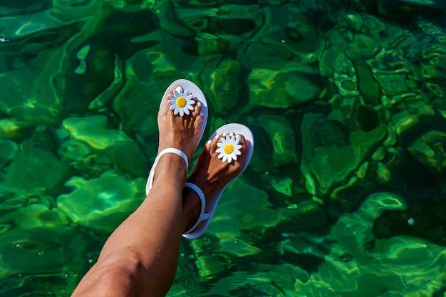 夏の日は、オリジナルのサンダルを履いた足が水上にあります。背景にエメラルド色のきれいな海水。