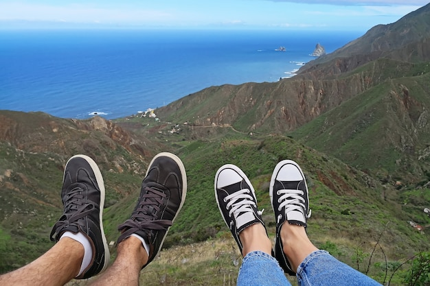Feet of woman and man dangling off of a cliff over the ocean.
