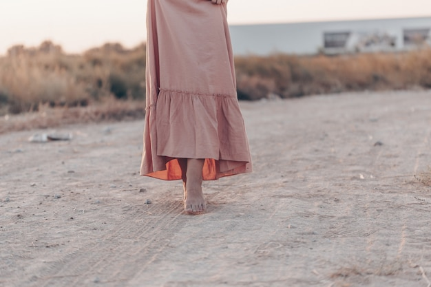 Feet of a woman in a pink dress walking on the sand during sunset