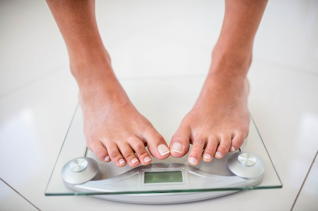 Feet of woman on weighting scale at home