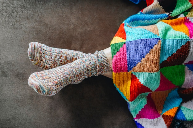 Feet of a woman with socks on a brown sofa covered with a patchwork blanket