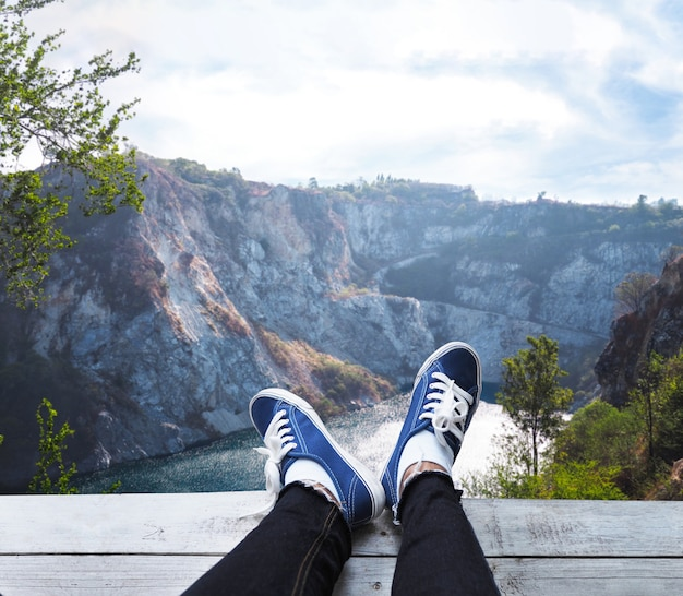Feet on wooden floor over high mountain and blue lake background.