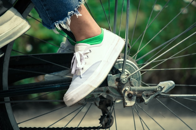 Feet of young woman riding a bicycle