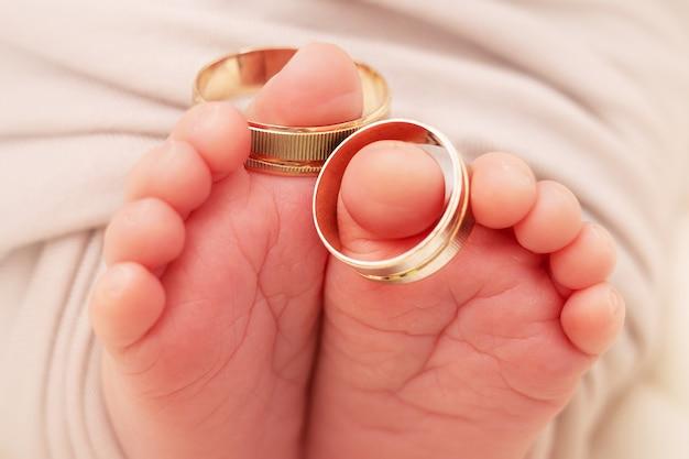 結婚指輪のクローズアップと生まれたばかりの赤ちゃんの小さなfeetsと指