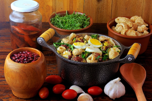 Feijao tropeiro typical dish of brazilian cuisine, made with beans, bacon, sausage, collard greens, eggs, on rustic wooden table.