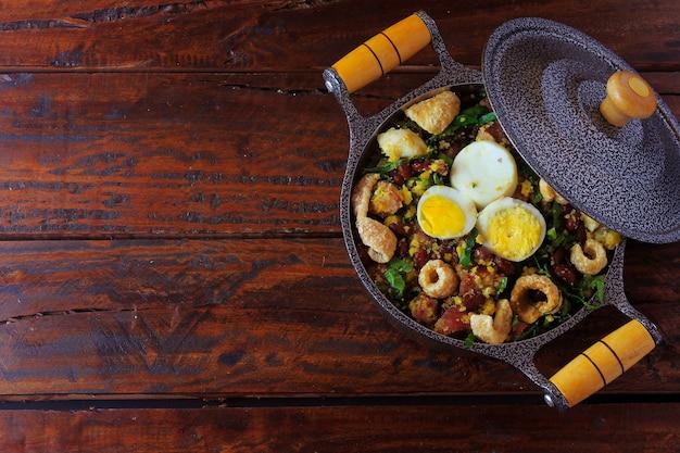 素朴な木製のテーブルの上に豆、ベーコン、ソーセージ、コラード、卵で作られたブラジル料理のフェイジャトロペイロの典型的な料理。