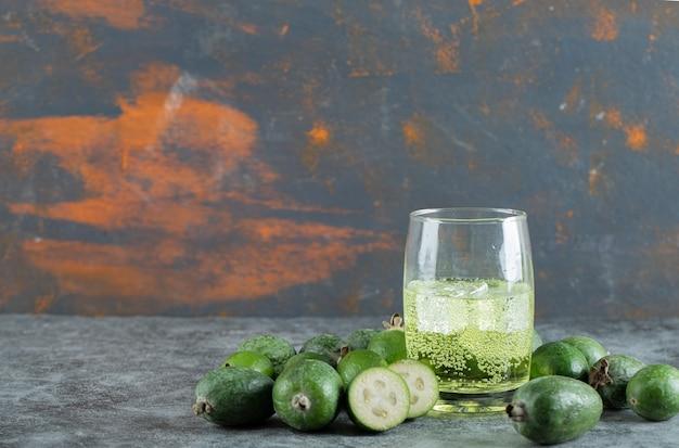Плоды фейхоа и стакан сока на мраморном столе. фото высокого качества
