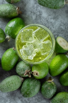 Feijoa fruits and glass of juice on marble surface.