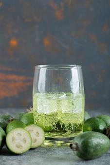 Frutti di feijoa e bicchiere di succo sul tavolo di marmo.