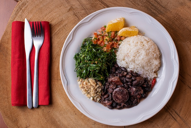 Блюдо фейжоада из черной фасоли, свинины и колбасы