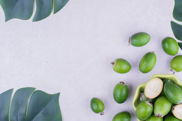Feijoas in una tazza verde su superficie grigia