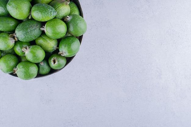 Фейхоа сложены в металлическую вазу на мраморном фоне. фото высокого качества
