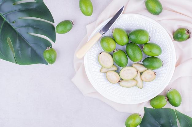 Feijoas in un piatto bianco su superficie grigia