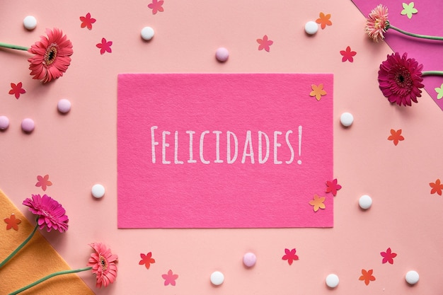 Felicidades는 스페인어로 축하를 의미합니다. 거베라 데이지 꽃으로 생생한 평평함