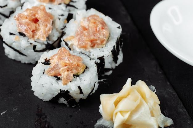 Ролл феликс с соусом васаби из тунца и маринованным имбирем на черной доске.
