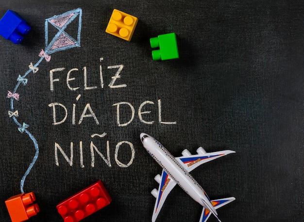 黒板に書かれたfeliz dia delniño(スペイン語)。おもちゃのアセンブリと飛行機の部品でkを描く