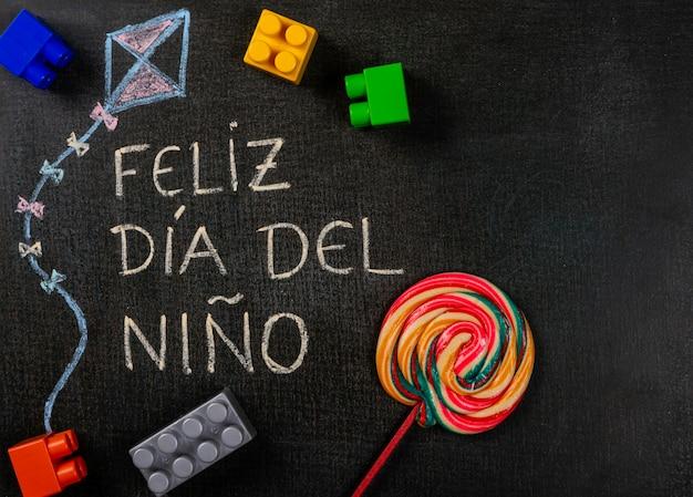 黒板に書かれたfeliz dia delniño(スペイン語)。組み立て部品とロリポップを使用したkのデザイン